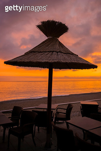 A Thatch Umbrella Over A Table With Chairs On The Beach At Sunset, Looking Out Over The Mediterranean Sea - gettyimageskorea