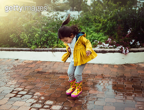 A three year old girl in a yellow jacket and flowered yellow and pink boots jumps in a puddle. - gettyimageskorea