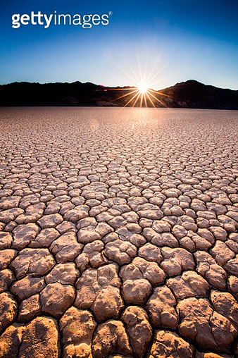 Cracked, dry ground leads to back lit mountains as sun bursts just above them - gettyimageskorea