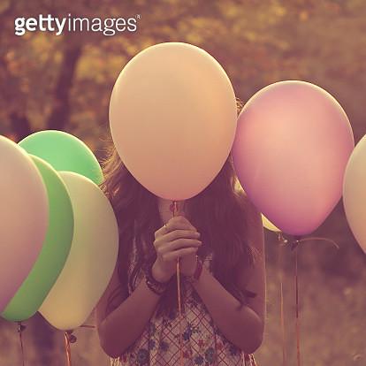 Girl hiding behind balloons - gettyimageskorea