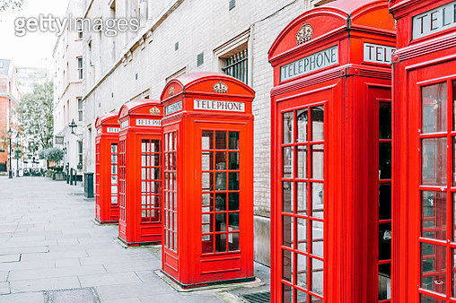 Red telephone boxes standing in a row on a street in London, The UK - gettyimageskorea