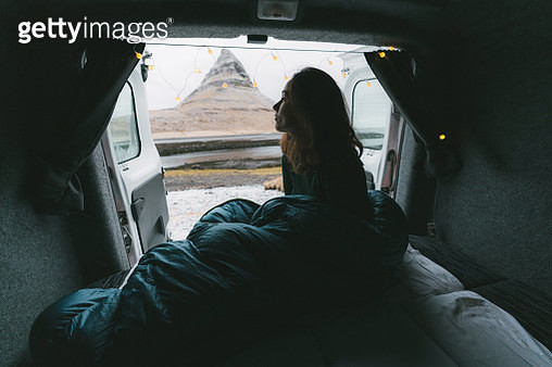 Woman in sleeping bag looking at Kirkjufell mountain from camper van - gettyimageskorea