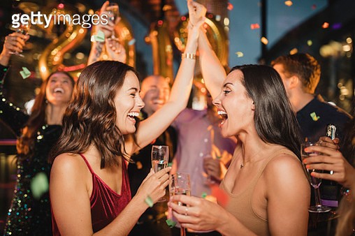 Two friends dancing among other people while celebrating the new year with a glass of champagne, balloons and confetti. - gettyimageskorea