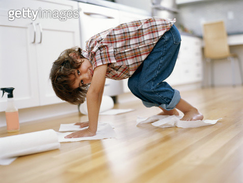 Boy (5-7) polishing floor with paper towel under hands and feet - gettyimageskorea