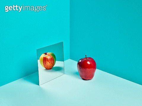 A Red Delicious apple in a mirror reflecting a mixed color apple made of slices of different varieties. - gettyimageskorea