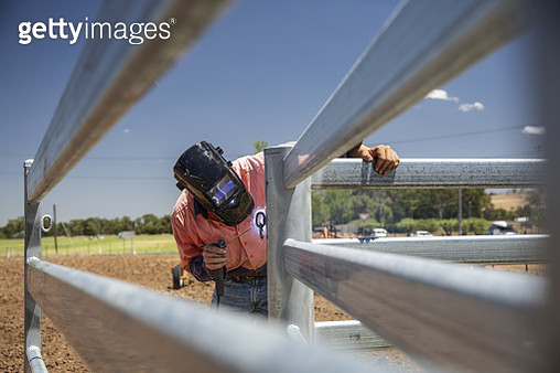 Man welding a fence on a farm - gettyimageskorea