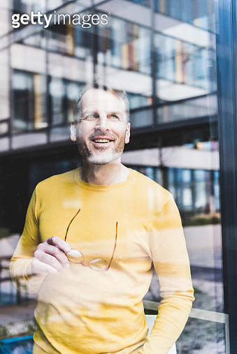 Happy casual businessman looking out of window - gettyimageskorea