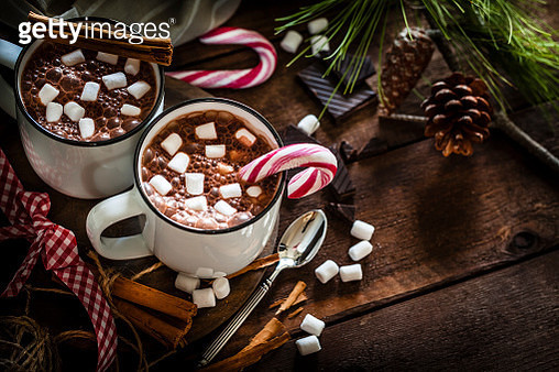 High angle view of two homemade hot chocolate mugs with marshmallows shot on rustic wooden Christmas table. A candy cane is inside one mug and another is placed directly on the table. Christmas decoration complete the composition. Low key DSRL studio phot - gettyimageskorea