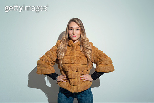 Young woman with blonde hair in yellow fur coat - gettyimageskorea