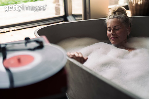 Mature woman taking bubble bath, listening music from analogue record player - gettyimageskorea