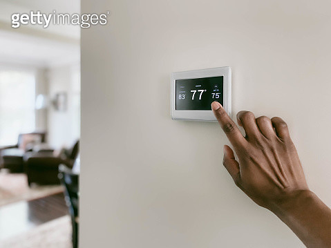 Woman Adjusts Thermostat - gettyimageskorea
