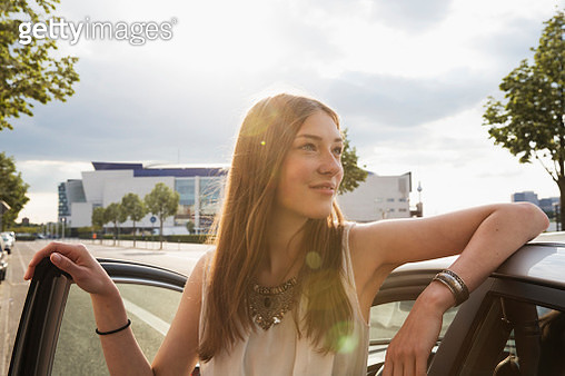 Young woman leaning at her car - gettyimageskorea