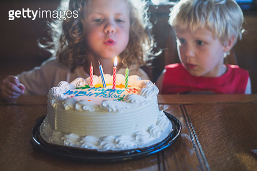 Kids Blowing Out Candles on Cake - gettyimageskorea