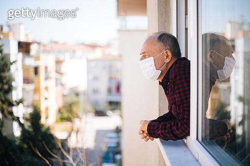 Senior man in medical mask on window breathing fresh air from quarantine - gettyimageskorea