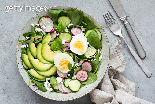 Healthy salad bowl with avocado, baby spinach, cucumber, radish and boiled egg. Table top view, concrete background - gettyimageskorea