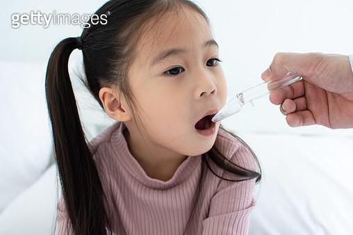 Cute little Child girl receiving pill at home - gettyimageskorea