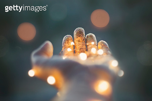 Holding hand open with glowing lights - gettyimageskorea