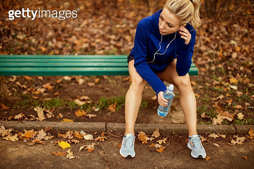 Female runner sitting on a park bench on an Autumn day taking a break - gettyimageskorea