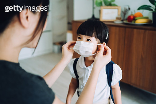 Young Asian mother preparing for her little daughter's first day of school and putting on a protective face mask on her daughter's face to protect and prevent from the spread of viruses - gettyimageskorea
