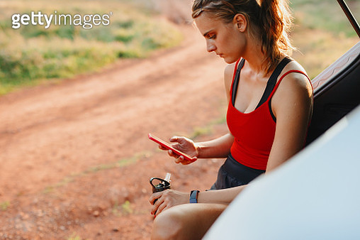 Sporty young woman using a cellphone while exercising - gettyimageskorea