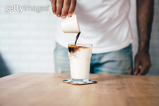 Man's hand pouring espresso to cold milk for ice latte - gettyimageskorea
