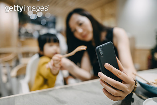 Joyful young mother and cute little daughter waving hands while video conferencing on smartphone during meal in a restaurant - gettyimageskorea