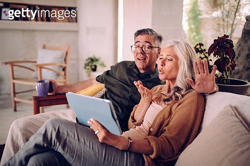 Mature couple relaxing at home and making video-call on tablet - gettyimageskorea