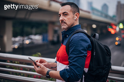Mature man with backpack is using wireless headset and mobile phone. - gettyimageskorea
