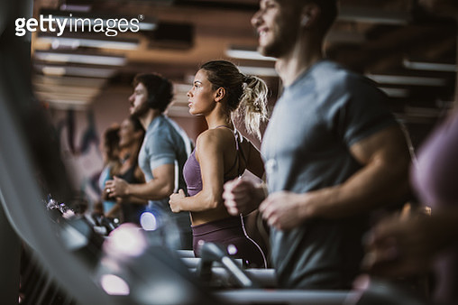 Young athletic woman running on treadmills in a gym full of people. - gettyimageskorea