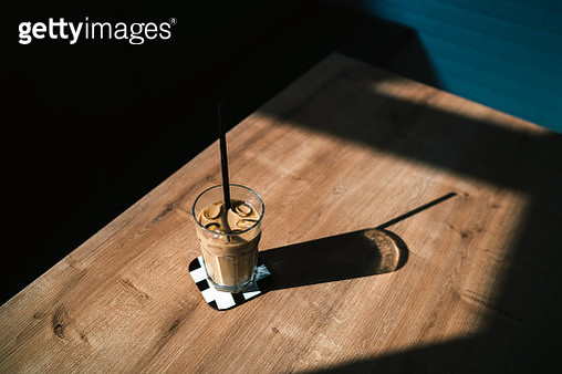 Dramatic shot of ice coffee at sunset with shadow - gettyimageskorea