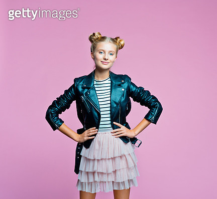 Female teenager wearing black leather jacket, pink tulle skirt and striped top standing with hands on hips. Studio shot on pink background. - gettyimageskorea