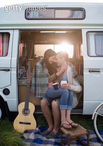 Couple together in camper van embracing. - gettyimageskorea