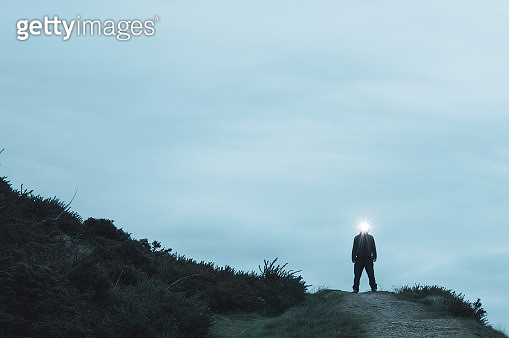 A scary silhouetted figure standing on the top of a path on a hill in the countryside, with a light glowing from his head. On a winters evening. - gettyimageskorea