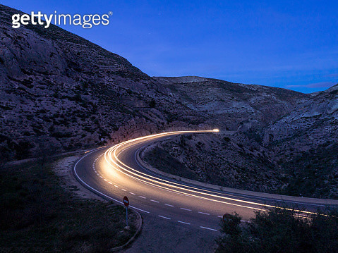 Lights of vehicles circulating along a road of mountain with curves closed in the night - gettyimageskorea