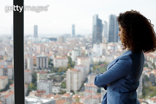 Thoughtful businesswoman looking through window - gettyimageskorea