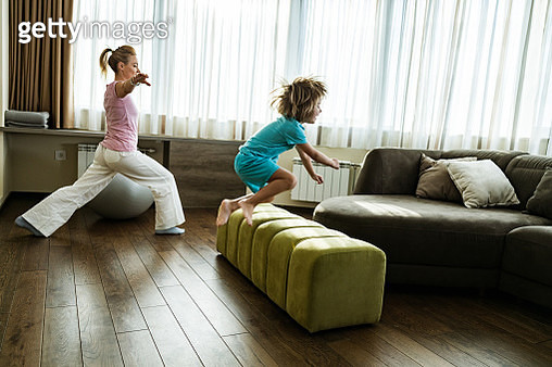Single mother and her small son having a sports training in the living room. Mother is exercising balance while happy boy is exercising jumps. Copy space. - gettyimageskorea