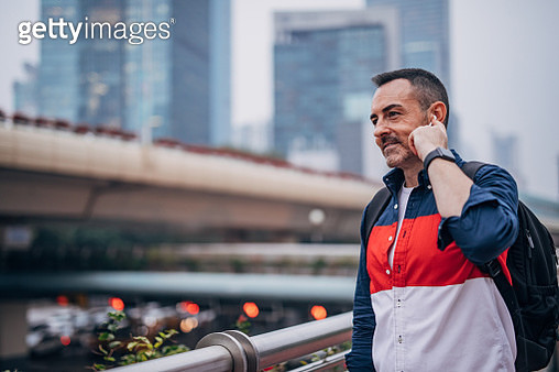 Mature man with backpack is using wireless headset. - gettyimageskorea