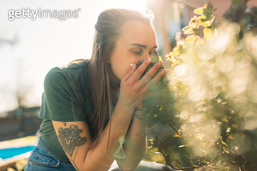 Young woman smelling at herbs in garden - gettyimageskorea