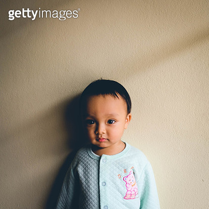 Close-Up Portrait Of Baby Boy Standing By Beige Wall - gettyimageskorea