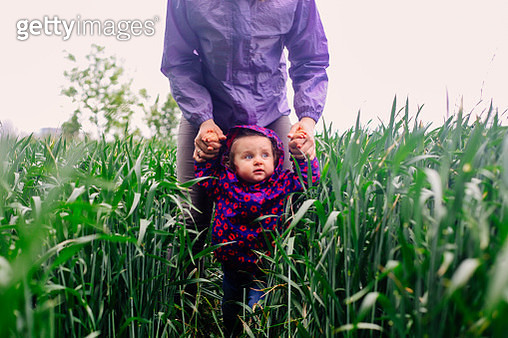 Little kid small girl walking in the vibrant green field being held by her mother. Childhood and family concept. - gettyimageskorea