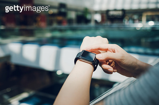 Close up of woman checking the shopping list on smart watch in a shopping mall - gettyimageskorea