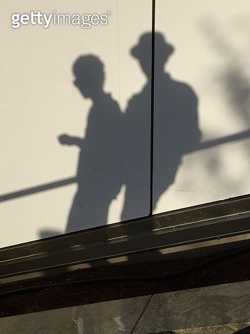 Shadow People: A couple relaxing on an outdoor railing - gettyimageskorea