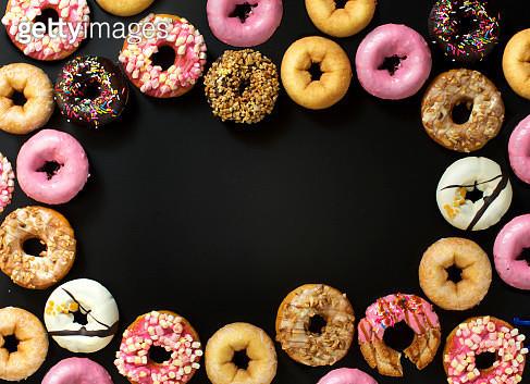 Assorted colourful glazed donuts frame on black background. - gettyimageskorea