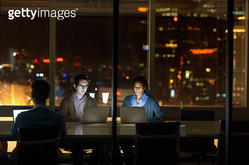 Colleagues working on laptops at night in office - gettyimageskorea
