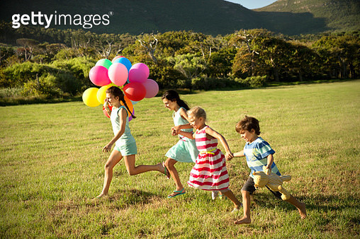 Happy children running with balloons on meadow - gettyimageskorea