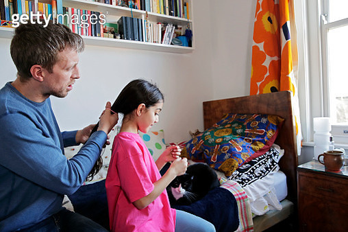 Father tying his daughter's hair in a ponytail - gettyimageskorea