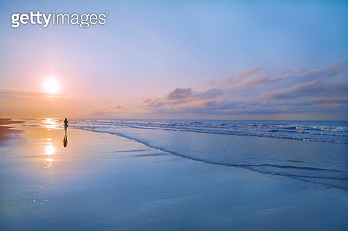 Person walking on beach at sunrise - gettyimageskorea