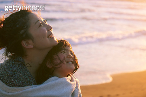 mother and her daughter are holding together in front of the beach - gettyimageskorea