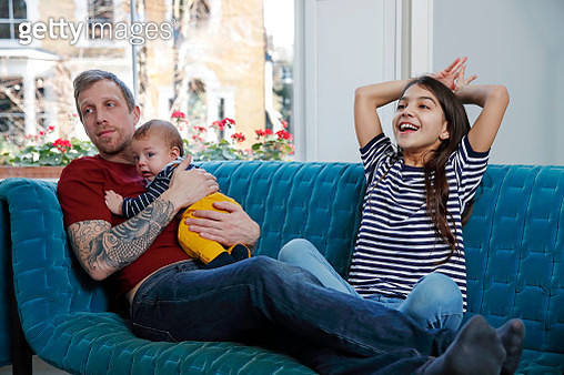 Mixed race girl sitting on sofa with father and baby brother - gettyimageskorea