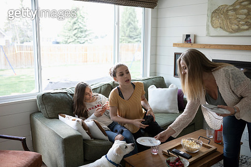 Mother and teenage daughters in living room, playing video game - gettyimageskorea